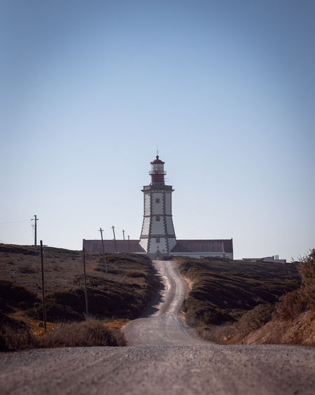 Lighthouse Road Autumn Fall Tower Travel Safety Security Protection Architecture Direction Outdoors Blue Orange Moody Guidance Building Vertical Leading Lines Land No People Clear Sky Sky Day Gravel