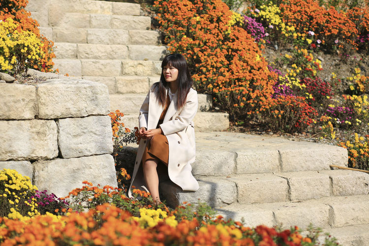 Full length portrait of woman sitting on stone wall