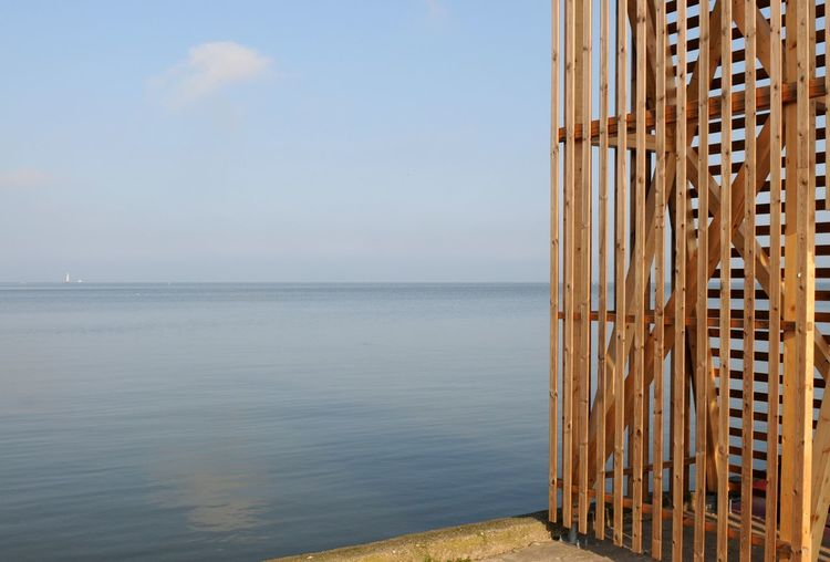 Wooden structure on pier by sea against sky
