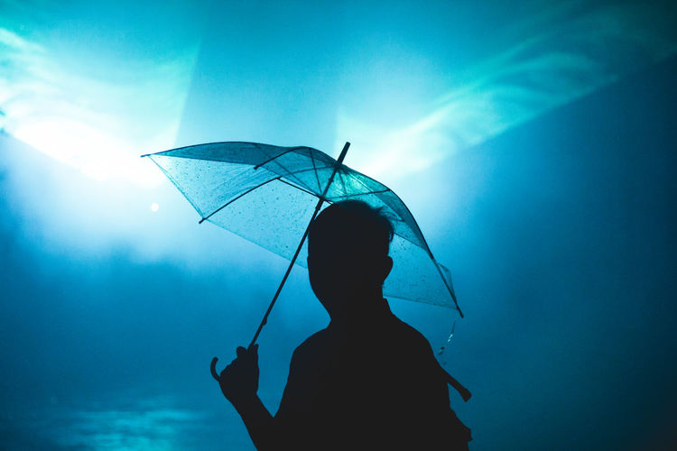 Silhouette man with umbrella standing against blue water