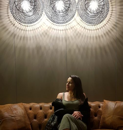 Woman sitting on sofa in illuminated room