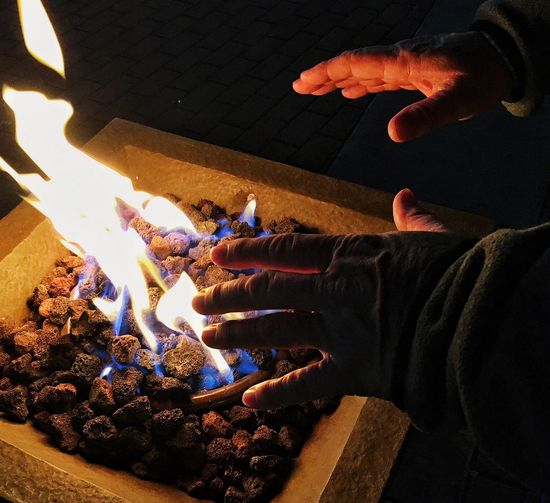 Cropped Image Of Person Warming Hands At Fire Pit