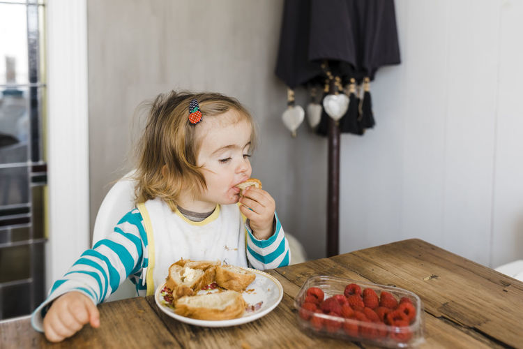 Toddler girl eating pastries instead of raspberries - Hindeloopen, Netherlands Addict Baby Bib Biting Blond Bread Breakfast Caucasian Chair Child Childhood Choice Close-up Croissant Decision Dining Eating Education Face Food Fruit Girl Hand Happy Headshot Healthy Holding Home Hungry Indoors  Indulgence Joy Kid Learning Lunch Netherlands Pastry People Plate Portrait Raspberry Room Sitting Snack Sweet Table Temptation Toddler  Unhealthy Food And Drink One Person Real People Healthy Eating Home Interior Innocence Lifestyles Freshness Girls Females