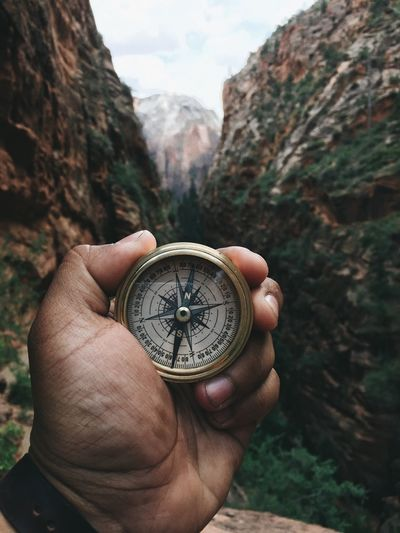 Navigating through the mountains Human Hand Human Body Part Navigational Compass Human Finger Holding One Person Real People Unrecognizable Person Adventure Personal Perspective Direction Mountain Men Exploration Time Day Close-up Outdoors Nature People Compass Adventures Explore