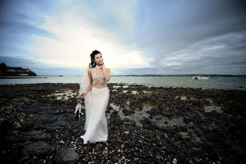 Full Length Of Smiling Bride Holding High Heels While Standing At Beach