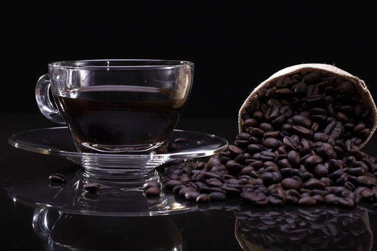 A cup of coffee with coffee beans over the black background Food And Drink Black Background Coffee - Drink Indoors  Coffee Drink Studio Shot Still Life Refreshment Freshness Roasted Coffee Bean Close-up Glass Mug Crockery Transparent Glass - Material Cup No People Food Caffeine