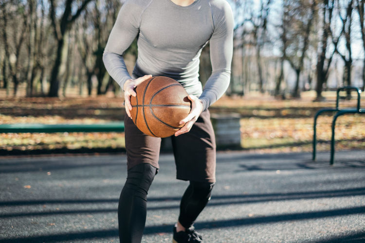 Midsection Of Man Playing Basket Ball On Sunny Day