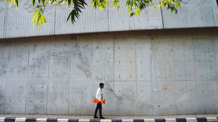 Full length of boy walking on footpath against wall