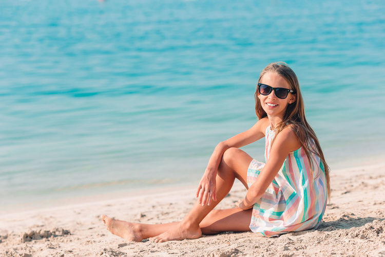 Portrait of young woman wearing sunglasses on beach