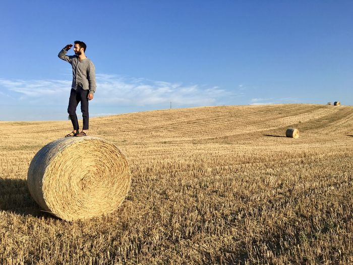 Man with hay bales on field against sky