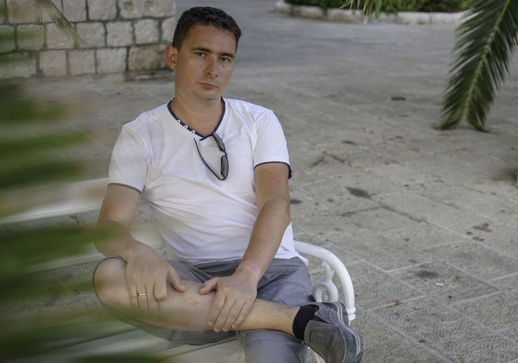 Portrait of mature man sitting on bench
