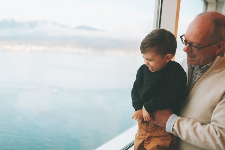 Cheerful man holding grandson looking through window against sea