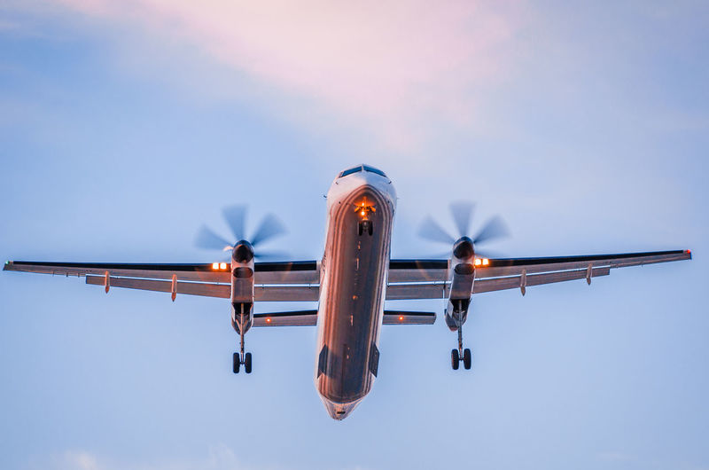 Low angle view of airplane against sky at dusk