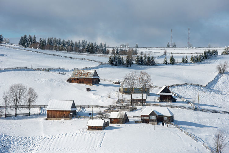 Houses on snow covered land against sky
