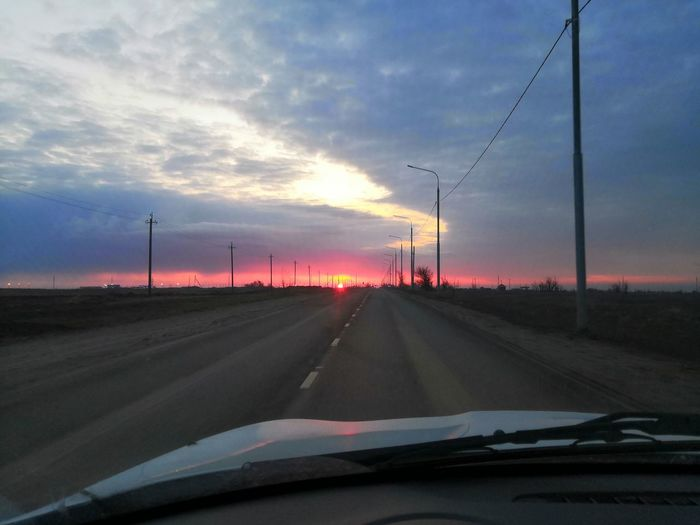 Road against sky seen through car windshield during sunset