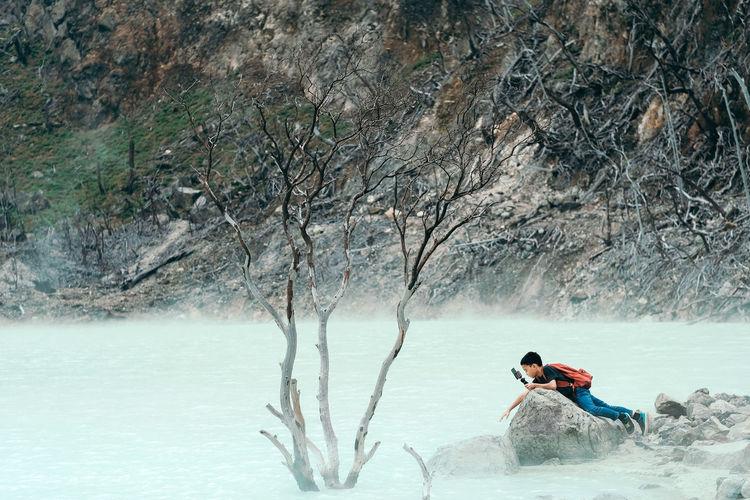 Side view of boy lying on rock in river