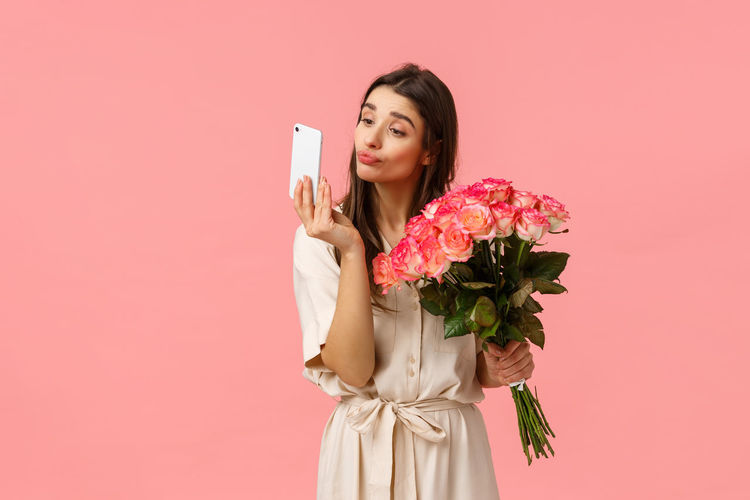 Young woman holding pink rose against gray background