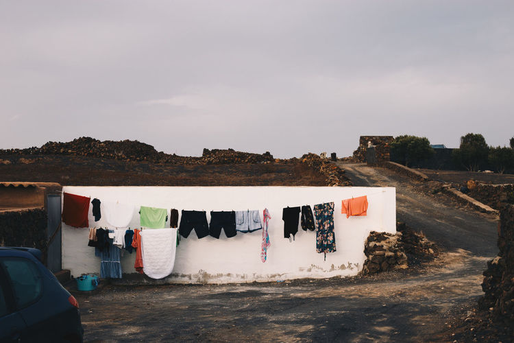 Clothes drying on clothesline outside building against sky