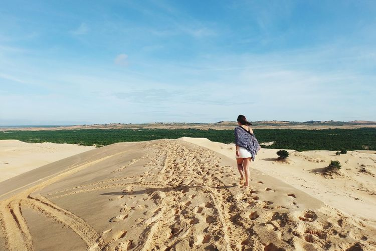 Rear view of woman walking on sandy beach against sky