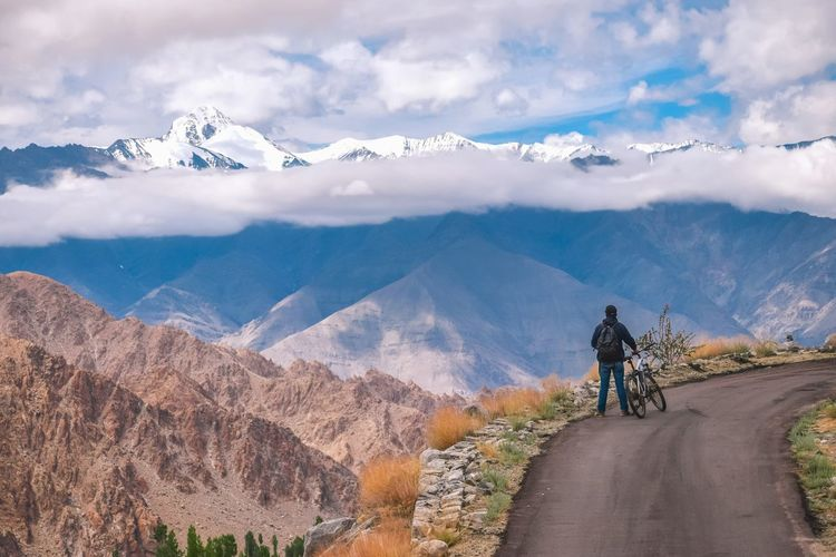 Man riding bicycle on mountain road against cloudy sky