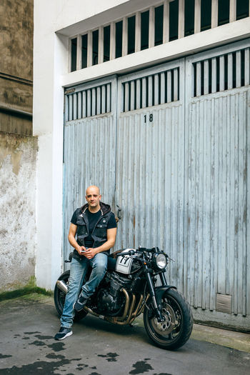 Mechanic with motorcycle at garage