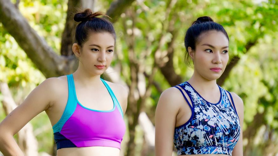 Portrait of young woman exercising with yoga instructor at park