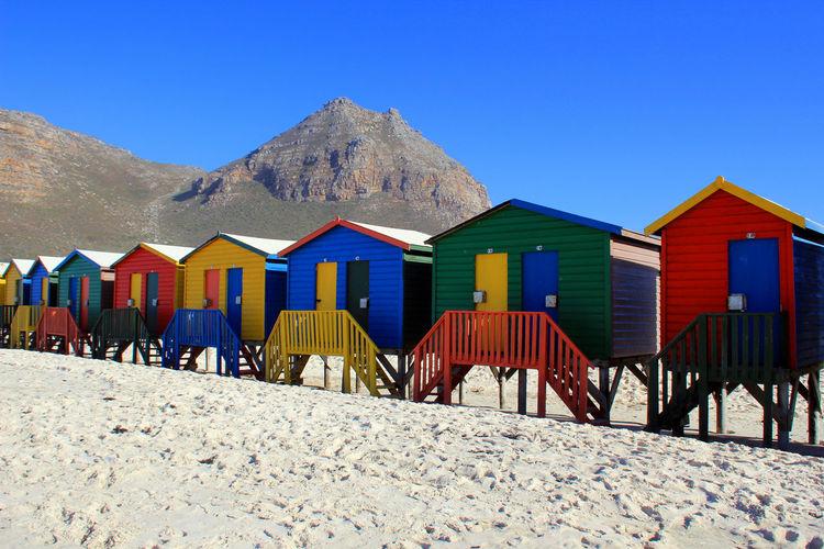 Beach huts on sand against clear sky