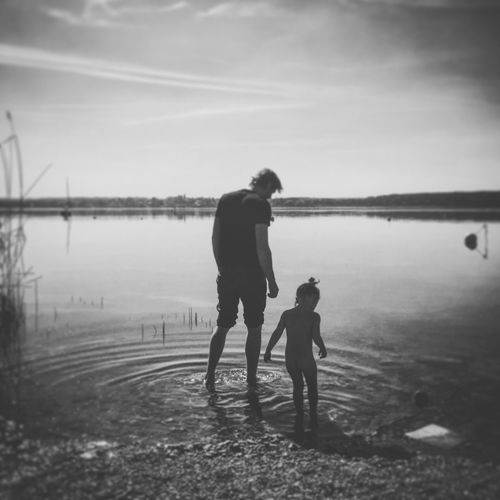 Rear view of father and daughter standing at beach against sky