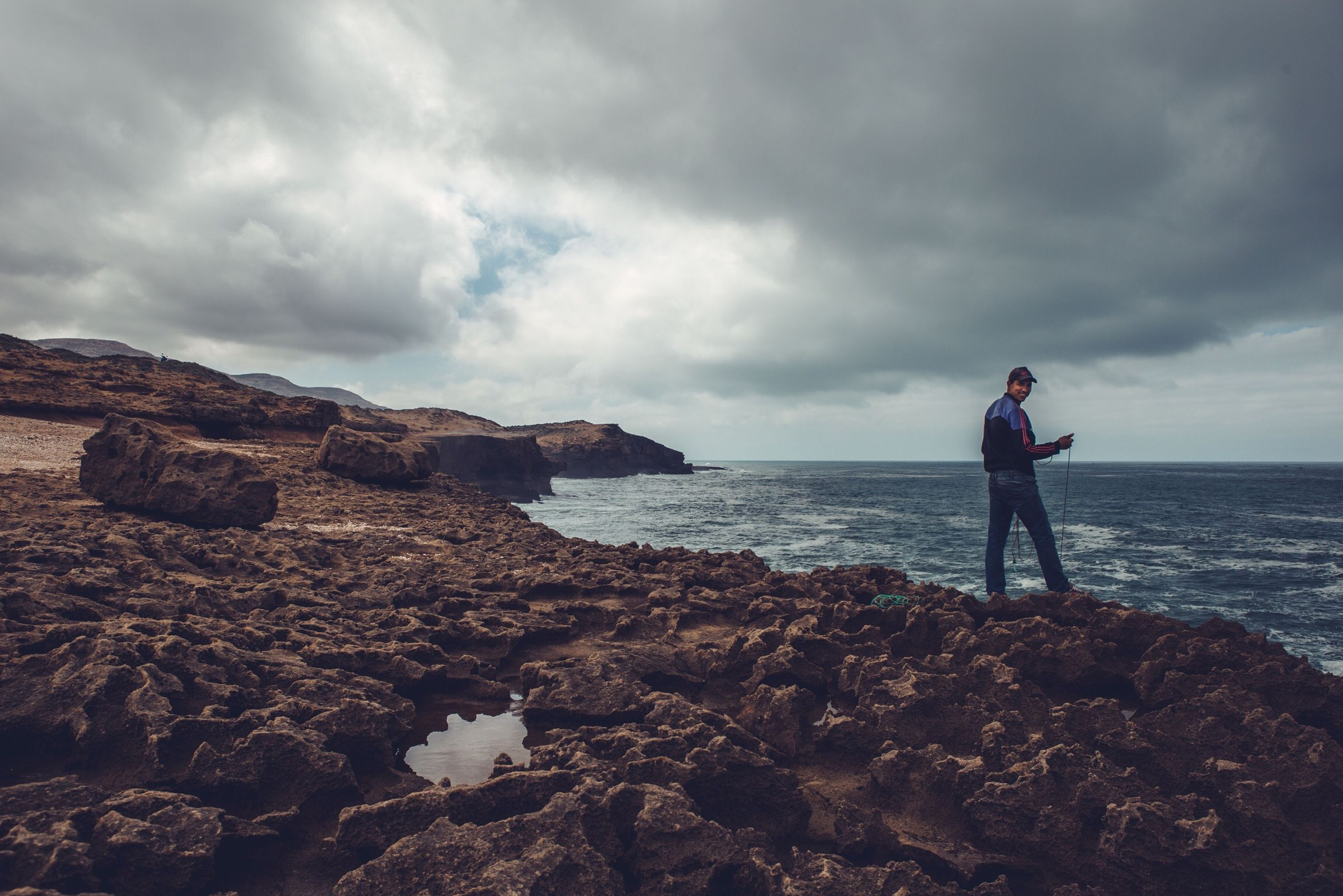 rock, cloud - sky, sky, rock - object, solid, water, sea, standing, one person, scenics - nature, beauty in nature, beach, real people, horizon, land, nature, horizon over water, outdoors