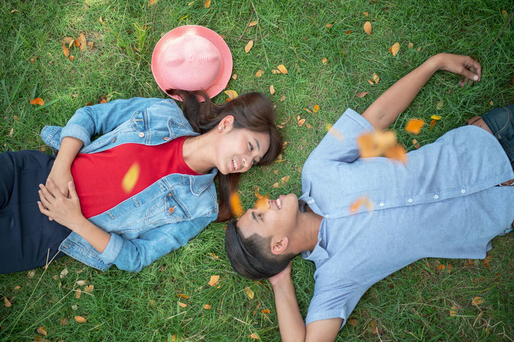 High angle view of friends lying on field