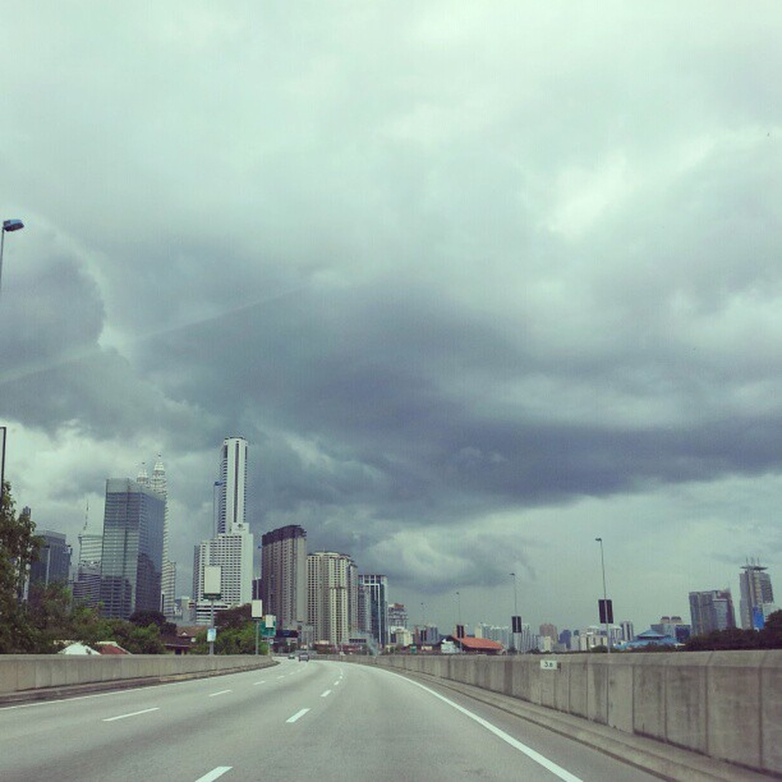 building exterior, sky, architecture, cloud - sky, cloudy, built structure, city, road, transportation, weather, overcast, street, the way forward, car, land vehicle, storm cloud, cityscape, cloud, road marking, city life