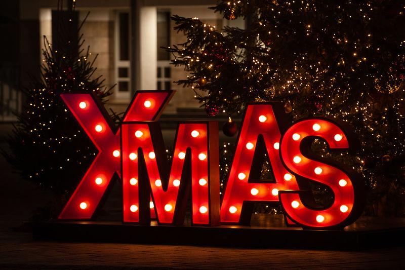 Text on illuminated christmas tree at night