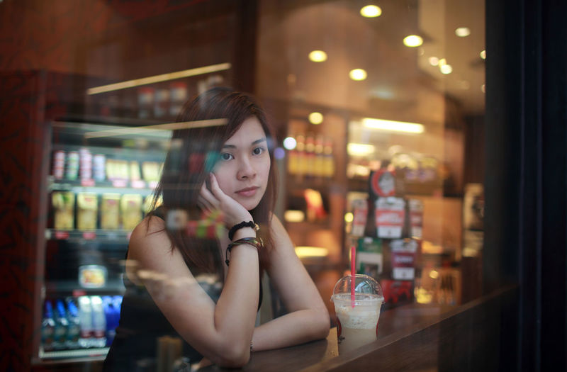 Thoughtful young woman looking through window at cafe