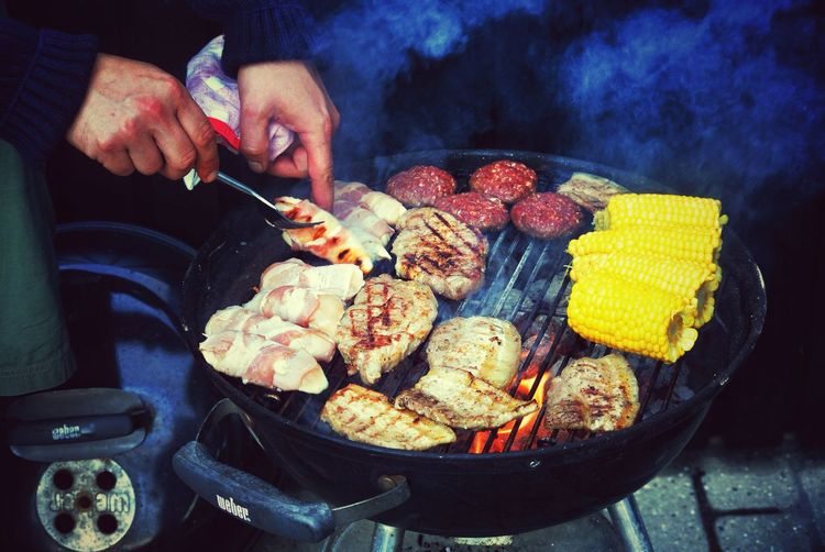 Cropped Image Of Man Barbequing Meat Outdoors