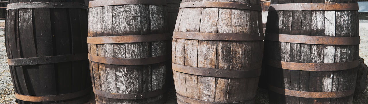 Old dirty weathered wooden barrels with rusty barrel hoops