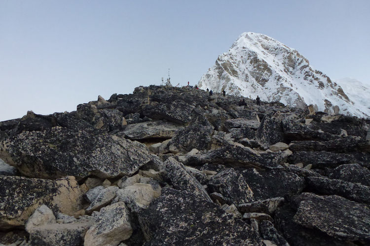 Low angle view of rocks on mountain against clear sky
