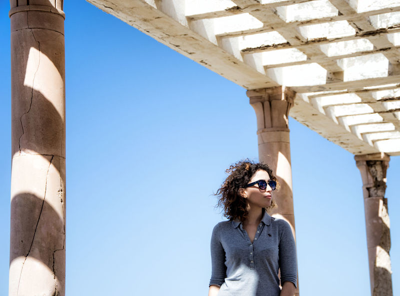 Architectural Column Architecture Blue Built Structure Casual Clothing Column Day Leisure Activity Lifestyles Outdoors Perspective Portrait Portrait Of A Woman Sky Standing Sunlight Sunny The Portraitist - 2016 EyeEm Awards Tourism Tourist Natural Light Portrait