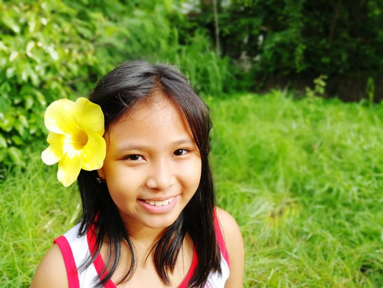 flower Looking At Camera One Person Smiling Portrait Headshot Toothy Smile Child People Children Only Happiness Black Hair One Girl Only Cheerful Childhood Fun Enjoyment Outdoors