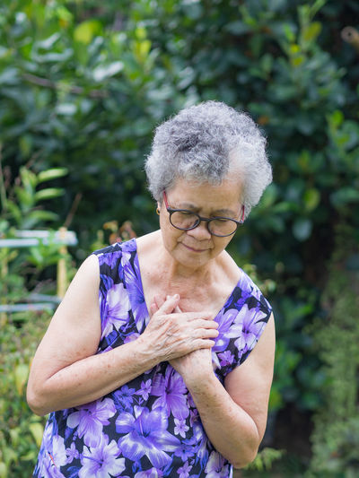 Portrait of elderly woman having heart attack.