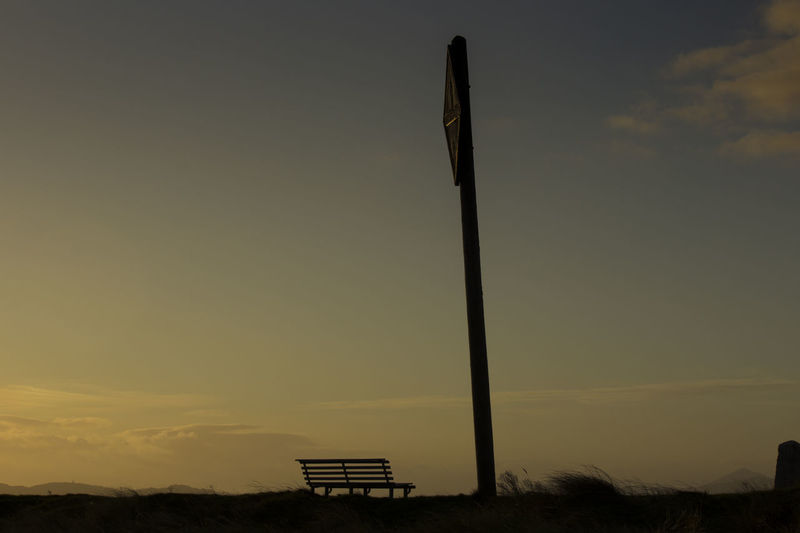 Silhouette pole and empty bench on field against sky at sunset
