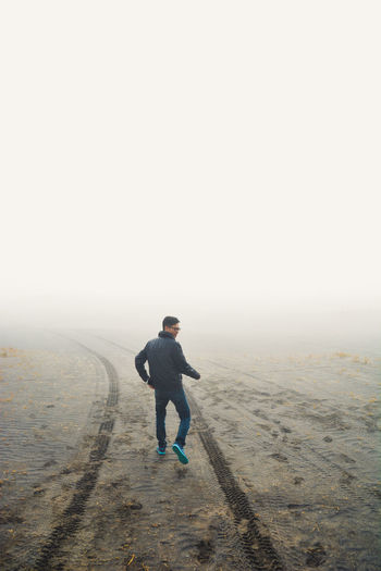 Full Length Rear View Of Man Walking On Sand In Foggy Weather