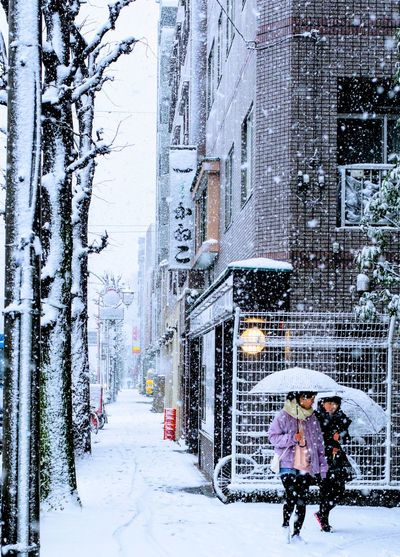 People walking on snow covered street in city