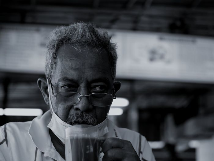 Portrait of man drinking glasses outdoors
