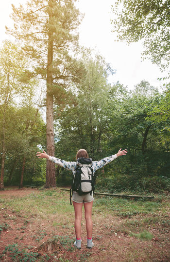 Full Length Of Young Woman With Arms Outstretched Standing In Forest