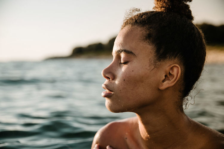 Close-Up Of Shirtless Young Woman Swimming In Sea Against Sky