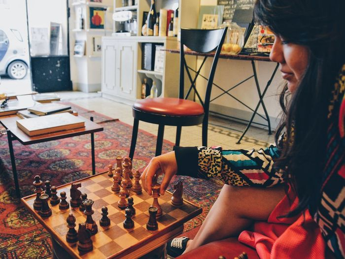 Woman playing chess at table in home