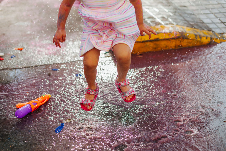 Low section of girl playing with toy in water