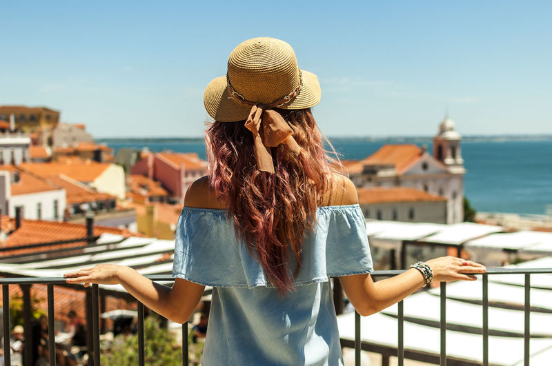 Rear View Of Young Woman Looking At Buildings And Sea While Standing By Railing In Balcony Against Clear Sky