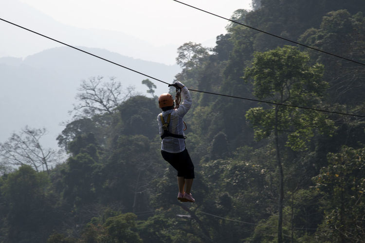 Person on zip line against tree mountains