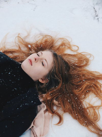 High Angel View Of Woman Lying On Snow